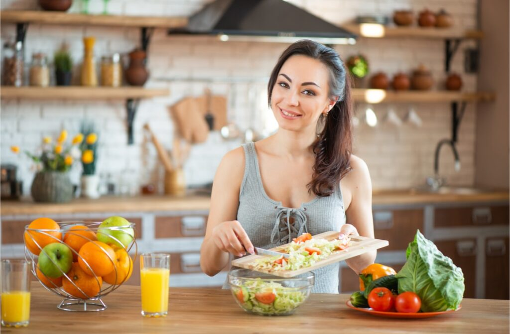 pretty young woman cutting vegetables
