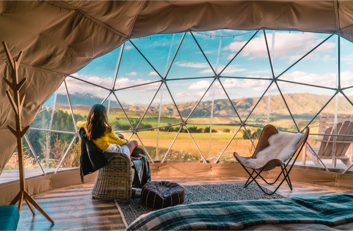 woman looking out at nature from geo dome tents