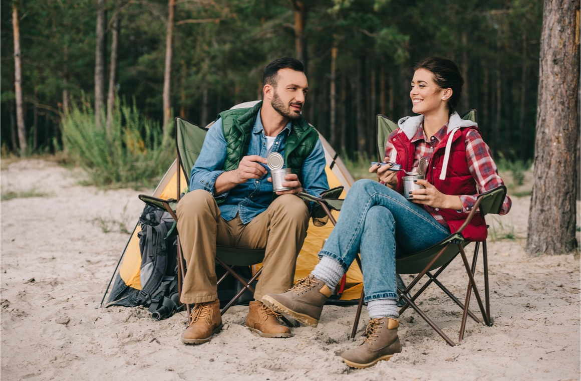 couple eating food from cans while having camping