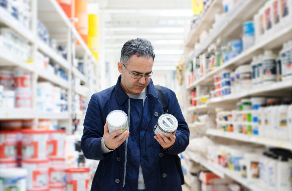 man choosing paints on hypermarket