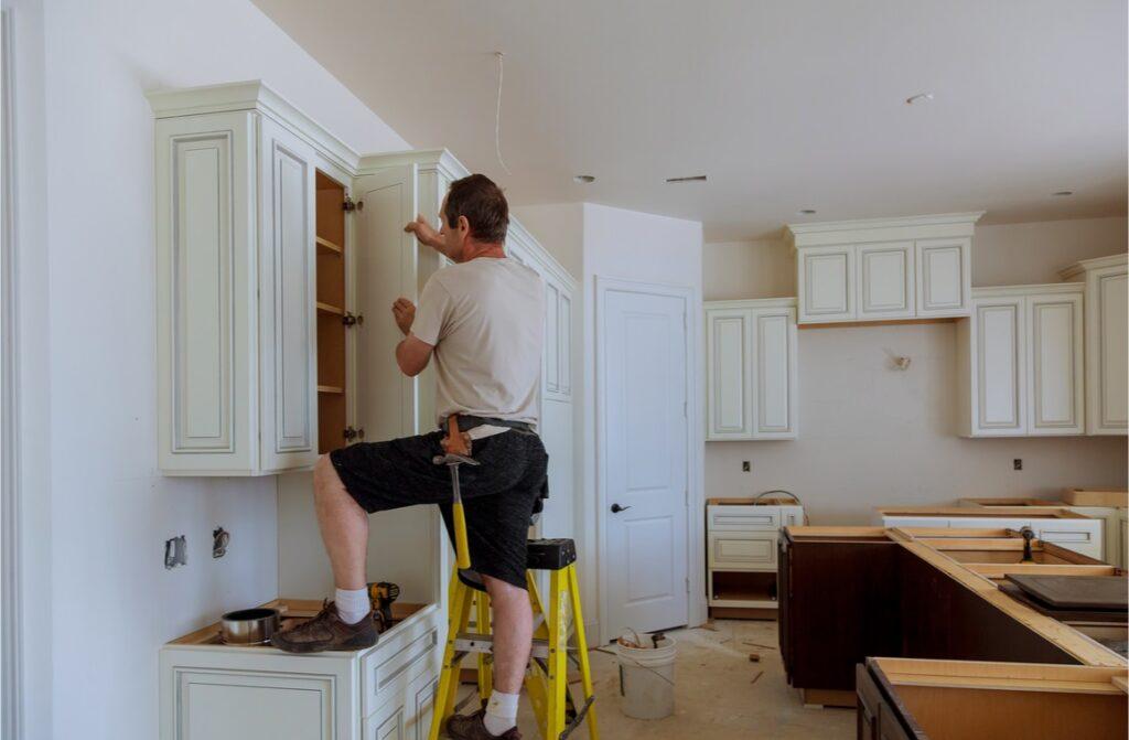 man installing cabinet doors