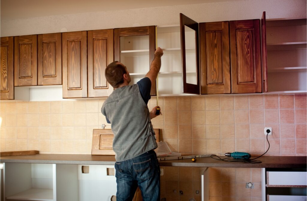 man working with new kitchen cabinets